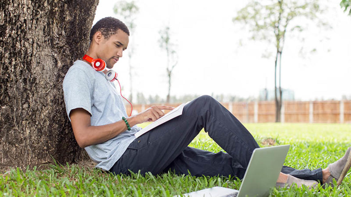 student studying by tree